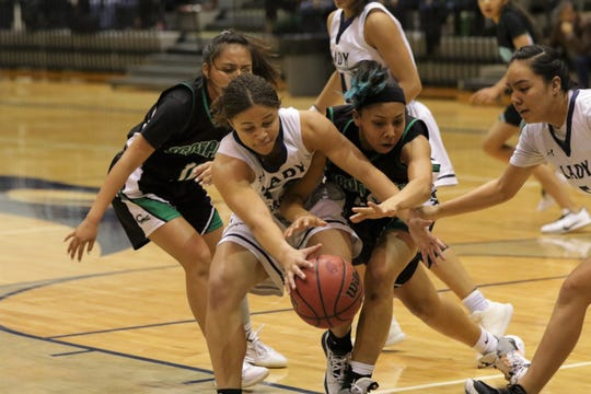 Piedra Vista's Celina Watson (14) and Farmington's Davina Begay (32) fight for the loose ball during Thursday's District 2-5A girls basketball tournament semifinals game at Jerry A. Conner Fieldhouse in Farmington.
