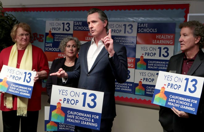 Gov. Gavin Newsom, center, speaks to the media in support of Proposition 13 at Vista Del Monte Elementary School in Palm Springs, Calif., on February 28, 2020 as City of Palm Springs Council Member Lisa Middleton, left, Palm Springs Unified School District Superintendent Sandra Lyon, Ed.D, and Mayor Geoff Kors listen.