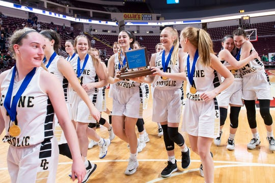 Delone Catholic seniors Maddie Sieg and Brooke Lawyer carry the District 3 Class 3A championship trophy off the floor of the Giant Center after the Squirettes defeated Trinity.