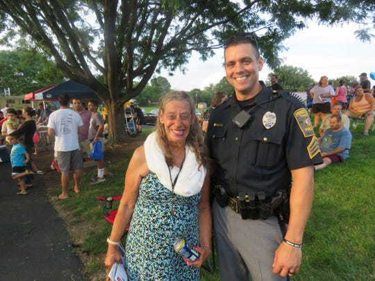 Officer Richard Thompson posses with a community member at a National Night Out event.