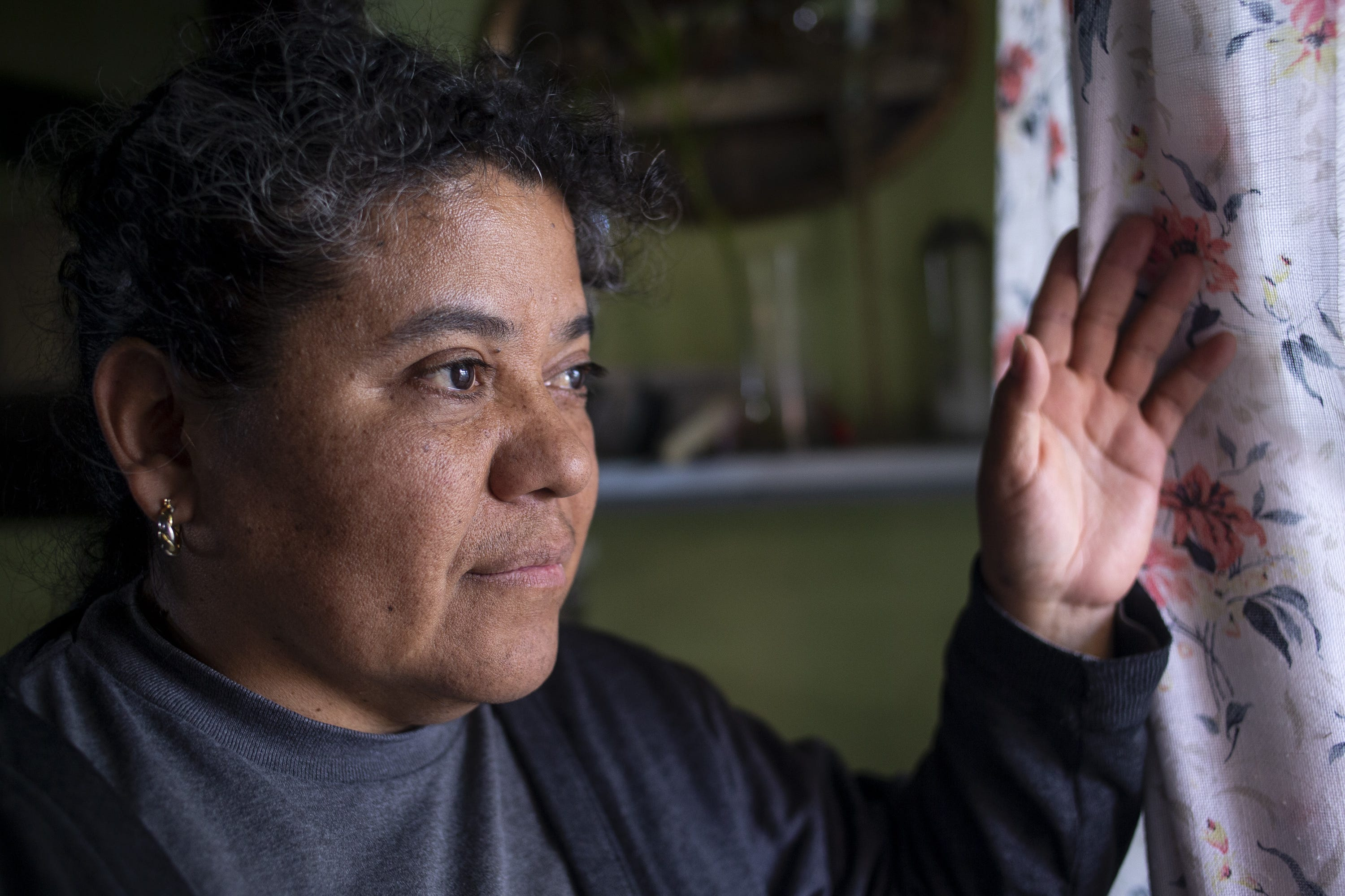 Blanca Abarca looks out the window of her home in South Phoenix.