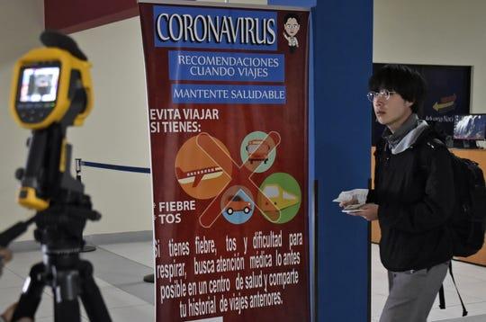 Una pancarta informativa sobre coronavirus puede verse en un aeropuerto.