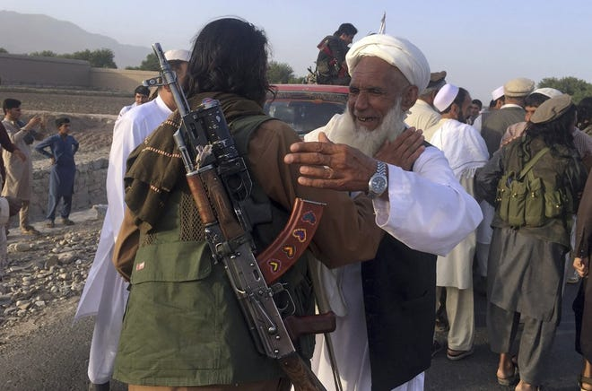 In this June 16, 2018 file photo, Taliban fighters gather with residents to celebrate a three-day cease fire marking the Islamic holiday of Eid al-Fitr, in Nangarhar province, east of Kabul, Afghanistan. Many Afghans view Saturday's expected signing of a U.S.-Taliban peace deal with a heavy dose of well-earned skepticism. They've spent decades living in a country at war -- some their whole lives — and wonder if they can ever reach a state of peace. (AP Photo/Rahmat Gul, File)