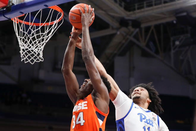Pittsburgh's Justin Champagnie (11) fouls Syracuse's Bourama Sidibe (34) during the first half of Wednesday night's game at Pitt. Sidibe had 13 points and 10 rebounds in Syracuse's 72-49 win.