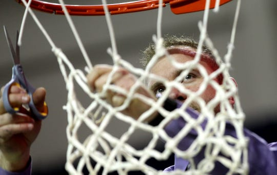 Sterling City head coach Cody Slate cuts down the net after a win against Rankin on Thursday, Feb. 27, 2020.