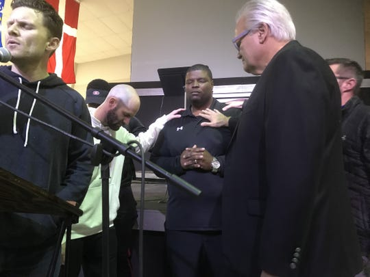 Evangel coach Byron Dawson is prayed over by the Eagles' coaching staff after announcing why he is leaving the school.
