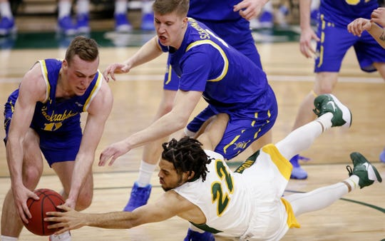 NDSU's Cameron Hunter dives for a loose ball as SDSU's Noah Freidel (left) tries to maintain control and Baylor Scheierman reaches in.