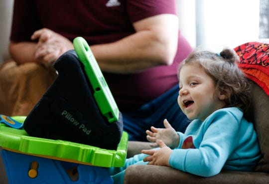 Two-year-old Regann Moore lights up as she watches videos on her iPad at home on Thursday, Feb. 20, 2020. Moore has a rare disease known as Krabbe Disease and received a life-saving stem cell donation less than a month after being born.