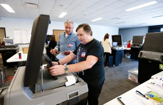 Daniel Cook (right) and Mike Schoonmaker verify a voting machine before sealing it at the Greene County Elections Center on Friday, Feb. 28, 2020.