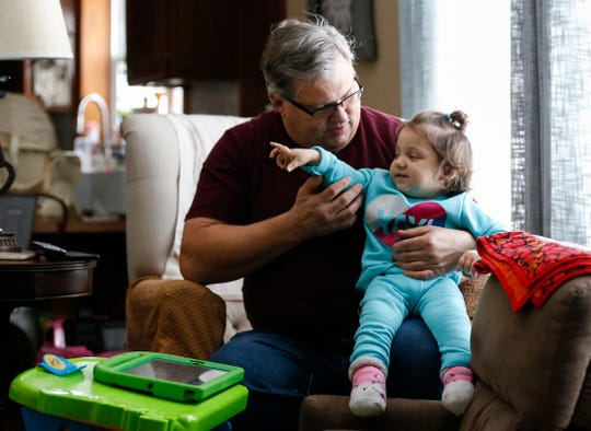 Ferrell Moore holds his two-year-old daughter Regann Moore at their home on Thursday, Feb. 20, 2020. Regann has a rare disease known as Krabbe Disease and received a life-saving stem cell donation less than a month after being born.