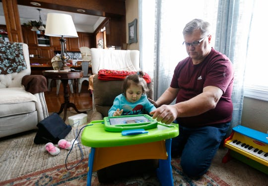 Ferrell Moore helps his two-year-old daughter Regann Moore with her iPad at their home on Thursday, Feb. 20, 2020. Regann has a rare disease know as, Krabbe Disease, and received a life-saving stem cell donation less than a month after being born.