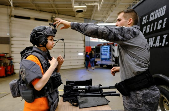 Foley student Caitlin Pare tries on SWAT team gear with the help of St. Cloud police officer Tyler Tabatt during the EPIC 2020 event Friday, Feb. 28, 2020, at St. Cloud Technical and Community College in St. Cloud.