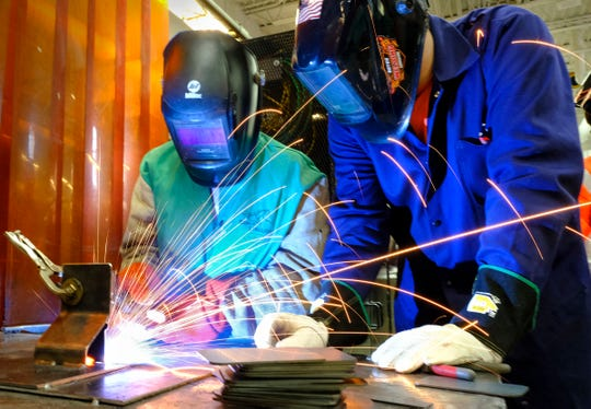 ROCORI student Avery Reitmeier welds a keepsake EPIC cutout of Minnesota with the help of instructor Brandon McAllister during the EPIC 2020 event Friday, Feb. 28, 2020, at St. Cloud Technical and Community College in St. Cloud.