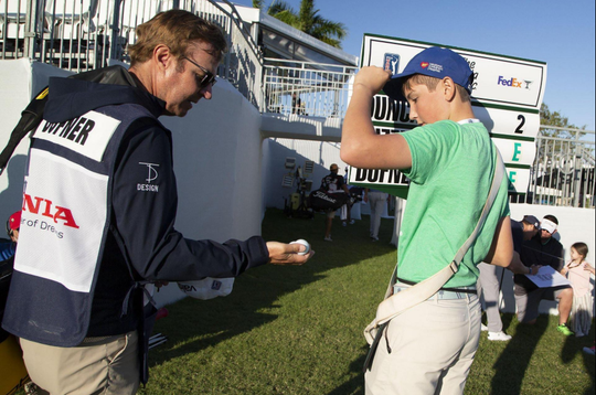 Henry Kuehne (right), 14, of Palm Beach Gardens, retrieves a ball from Jason Dufner's caddie following his round Thursday at the Honda Classic at PGA National in Palm Beach Gardens.