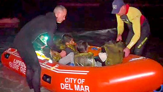 This photo from video provided by KGTV-10 News shows the rescue of some of 13 people after a suspected immigrant smuggling boat dropped the group off in the ocean on the Southern California coast early off Del Mar on Feb. 28, 2020. Up to three others may be missing.