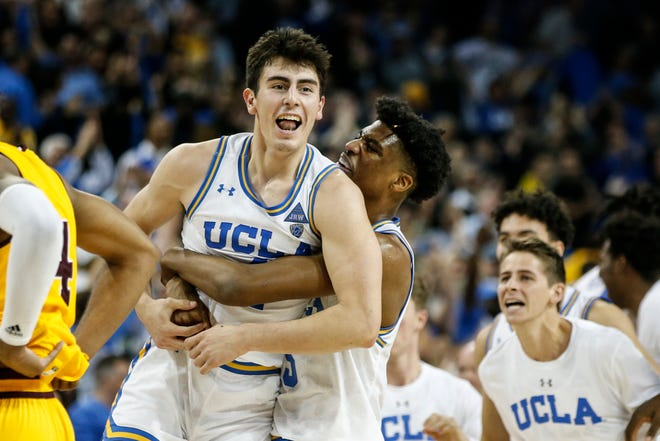 Camarillo High graduate Jaime Jaquez Jr. is hugged by UCLA teammate Jalen Hill after sinking a game-winning 3-pointer against Arizona State on Thursday night at Pauley Pavilion.