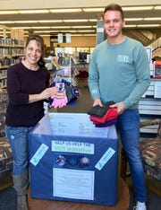 Danett Bolton, assistant, Cumberland County Library, and Christian Springer, library associate, donate new hats and mittens. Items collected at the library, 800 E. Commerce St., Bridgeton, through March 5 will be distributed to homeless individuals through the Cumberland County M25 Initiative. For information, call (856) 453-2210 or visit www.cclnj.org.