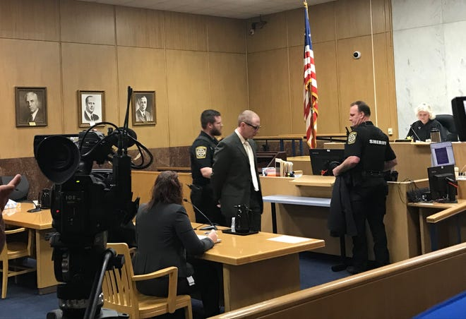 Former D.C. Everest high school teacher Travis Greil is led out of a Marathon County courtroom Friday following his initial appearance. He is accused of recording videos up high school girls' dresses and skirts.