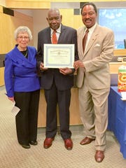 Legislators Harriet Cornell and then-Legislature Chair Toney L. Earl present the Distinguished Service Award to the Rev. Louis Sanders.