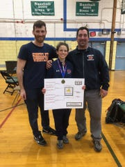 Horace Greeley's Isabella Garcia poses for a picture with coaches Anthony Tortora (left) and Mike DeBellis (right), after winning the PSAL girls' wrestling state tournament at 105 pounds.