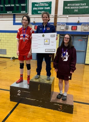 Horace Greeley's Isabella Garcia stands atop the podium, after winning the PSAL girls' wrestling state tournament at 105 pounds.