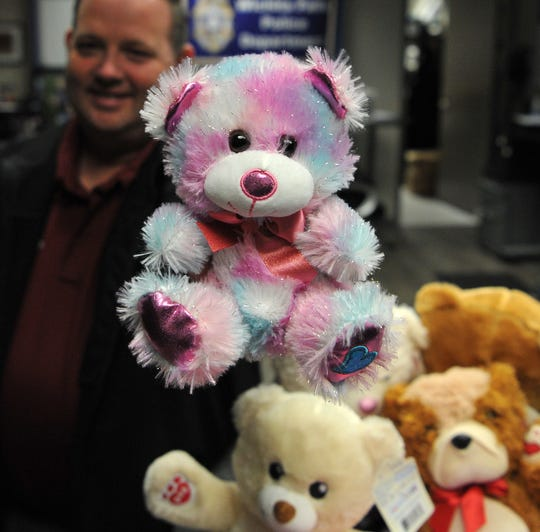 Wichita Falls police public information officer Brian Masterson holds one-of-several teddy bears donated to the department Friday morning.