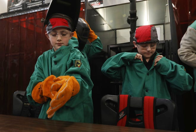 New Lexington Elementary School students Nate Elekes, 10, left, and Drew Anderson, 10, get ready to weld during a class at New Lexington High School recently. The class stemmed from the district's workforce development program.