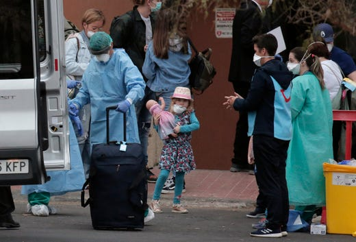 Health personnel wearing protection clothing assist guests as they leave the H10 Costa Adeje Palace hotel in La Caleta, in the Canary Island of Tenerife, Spain Feb. 28, 2020. Some guests have started to leave the locked down hotel after undergoing screening for the new virus that is infecting hundreds worldwide.