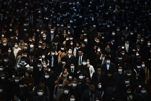 Mask-clad commuters make their way to work during morning rush hour at the Shinagawa train station in Tokyo on Feb. 28, 2020. Tokyo's key Nikkei index plunged nearly three percent at the open on February 28 after US and European sell-offs with investors worried about the economic impact of the coronavirus outbreak.