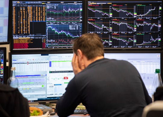 A broker watches his screens with the German stock index DAX in background at the stock market in Frankfurt, Germany,  Feb. 28, 2020.