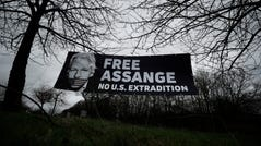 A banner put up by supporters, against the extradition of Wikileaks founder Julian Assange, hangs between trees outside a court in London, on Feb. 24, 2020.