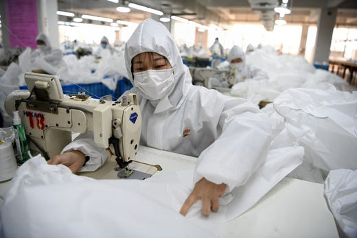 Workers sew hazardous material suits to be used in the COVID-19 coronavirus outbreak at the Zhejiang Ugly Duck Industry garment factory in Wenzhou on Feb. 28, 2020. The number of new cases of the COVID-19 coronavirus in China has declined in recent days, but infections in other countries have gathered pace.