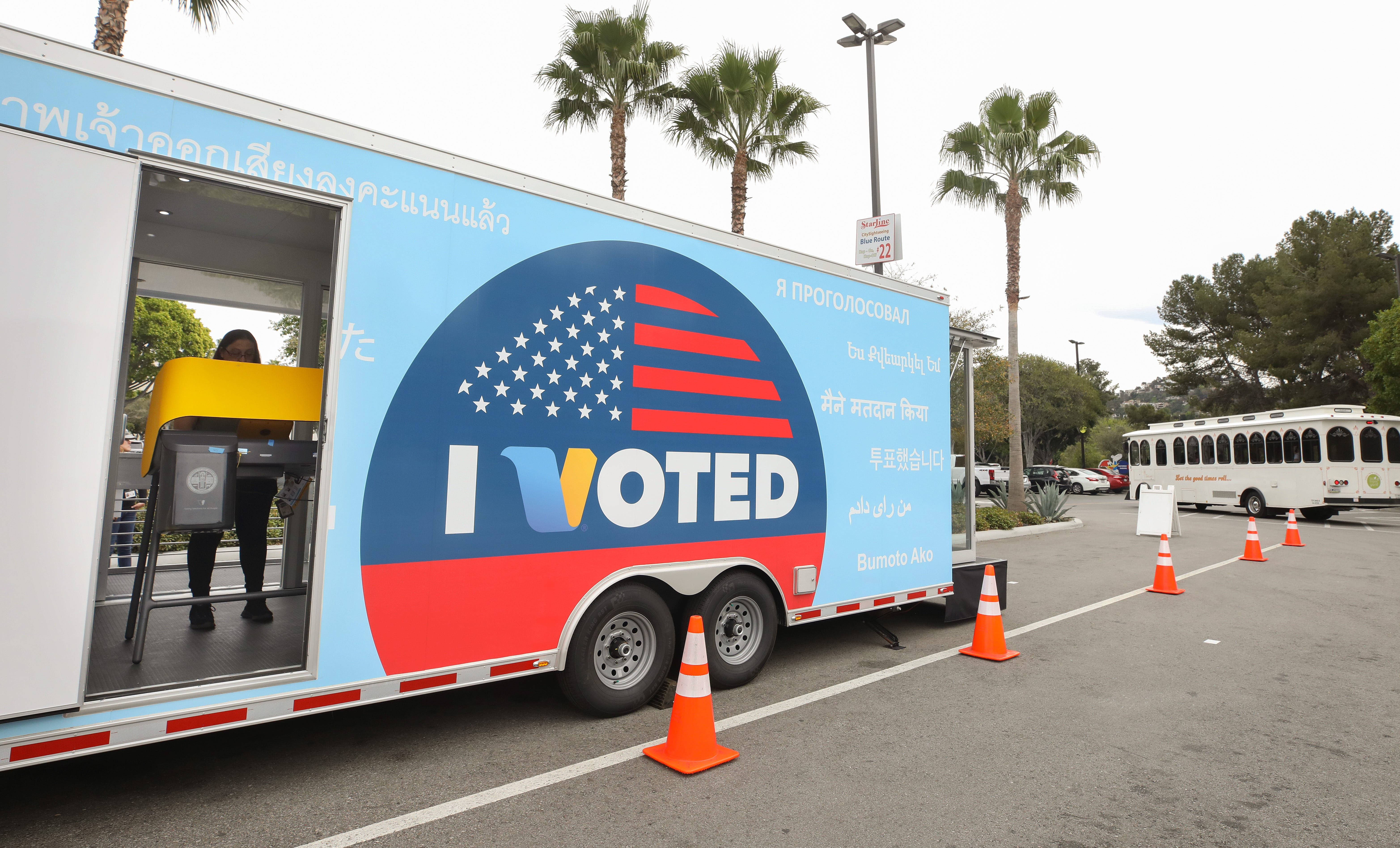 A voter prepares her ballot in a voting booth during early voting for the California presidential primary election at a new L.A. County Mobile Vote Center outside Universal Studios Hollywood