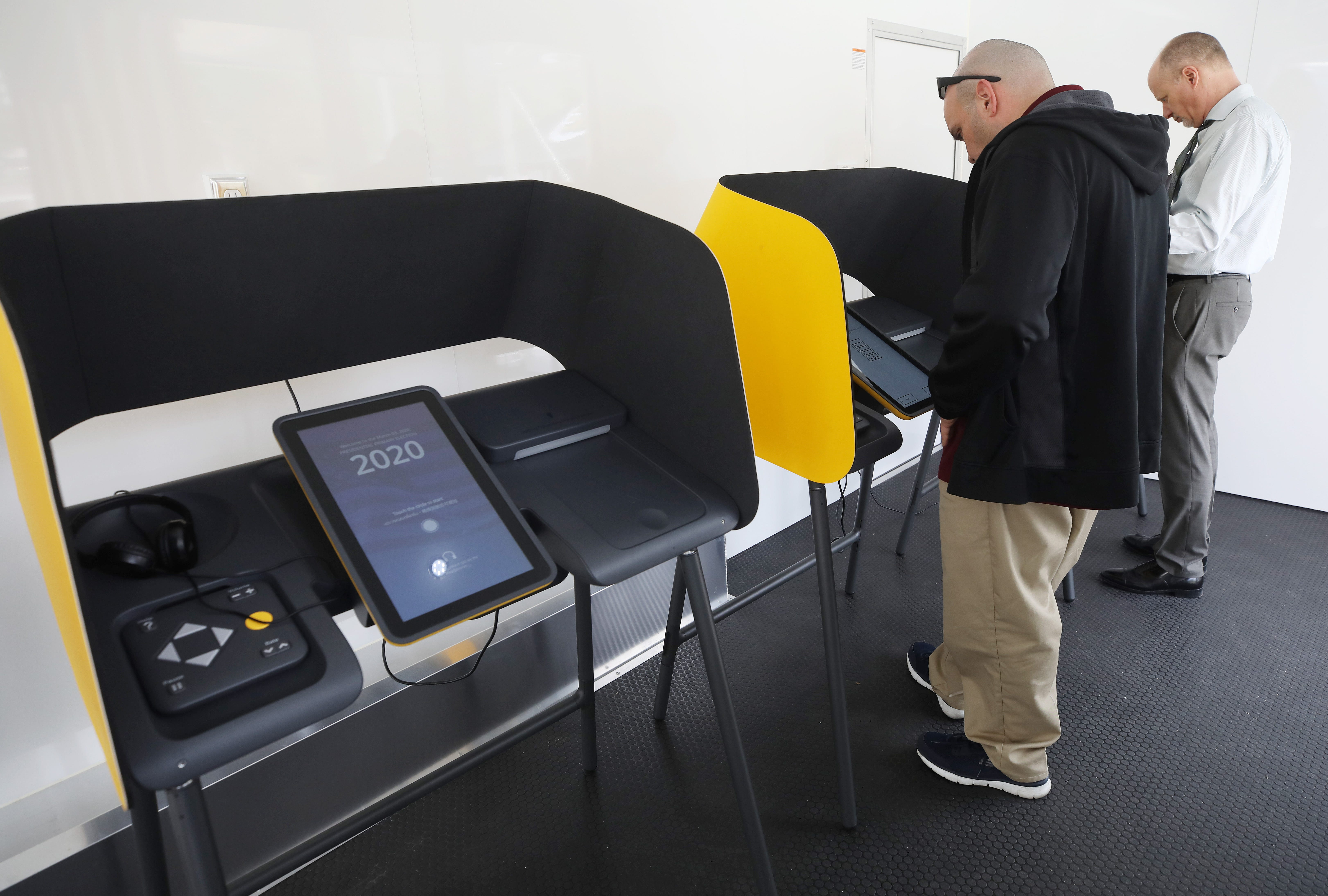 Voters prepare their ballots in voting booths during early voting for the California presidential primary election at a new L.A. County Mobile Vote Center