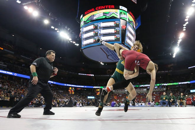 Ashwaubenon's Cody Minor throws Badger's Jake Stritesky in a Division 1 132-pound semifinal match Friday during the WIAA individual state wrestling tournament at the Kohl Center in Madison.