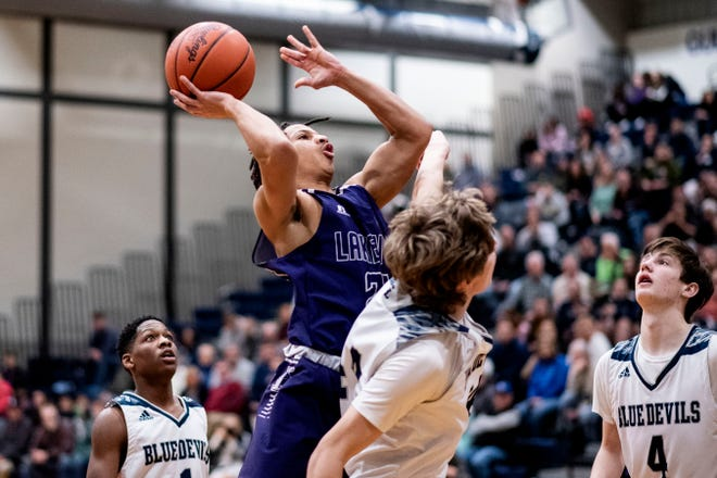 Lakeview senior Tommy Moore III (24) shoots the ball as Gull Lake senior Zach Pejka (44) guards him on Friday, Feb. 28, 2020 at Gull Lake High School in Richland, Mich.