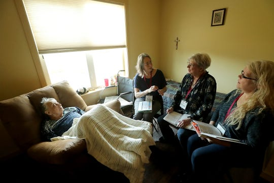 Madrona House resident Jean Cherry (far left) rests in her chair as The Agate Pass Threshold Choir's (left to right) Judy Friesem, Marilyn Price-Mitchell and Nancy Rudman sing in Cherry's room at the Madrona House on Bainbridge Island on Friday, Feb. 28, 2020.