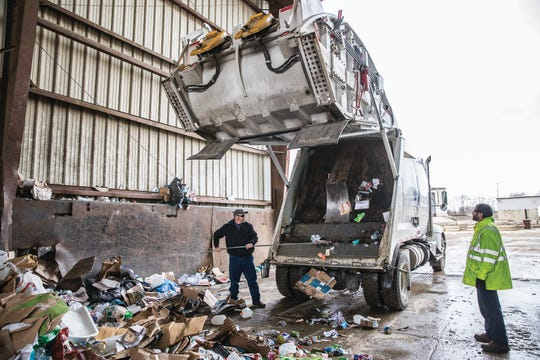 Recycling truck driver Matt Burns removes the extra recycling items stuck to the truck as they dump a truck full of recyclables at Rumpke Waste and Recycling on Feb. 28, 2020. The items will all be collected and sorted.