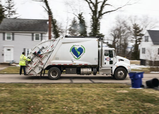 Workers stand on the back of the truck as they drive through town picking up cans of items to be recycled.
