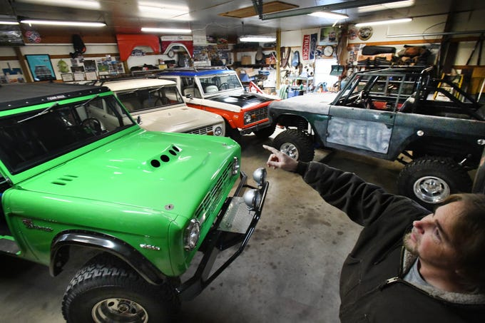 "Tom Carper in one of several garages he has filled with Broncos, parts and Ford Bronco collectibles at his ""Bronco Ranch."""