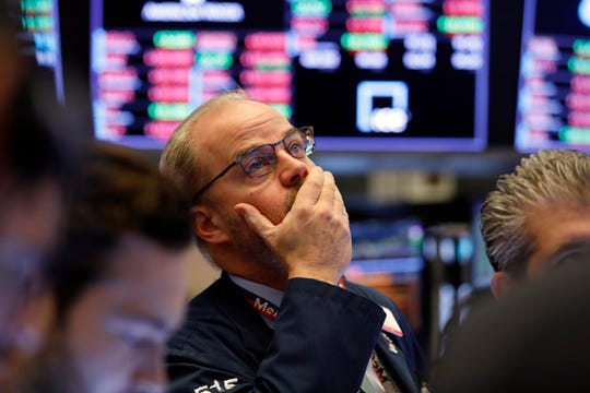 Trader David O'Day works on the floor of the New York Stock Exchange, Friday. Stocks sank again after another wild day, extending a rout that left Wall Street with its worst week since October 2008.