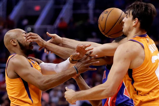 Phoenix Suns guard Jevon Carter, left, and forward Dario Saric battle with Pistons guard Brandon Knight for the loose ball.