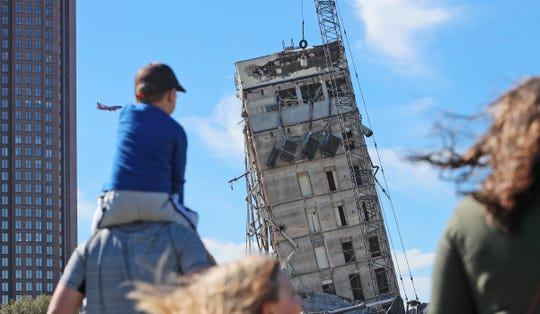 "People gather to watch the demolition of the so called ""Leaning Tower of Dallas"" as a wrecking ball works to topple the structure Monday."