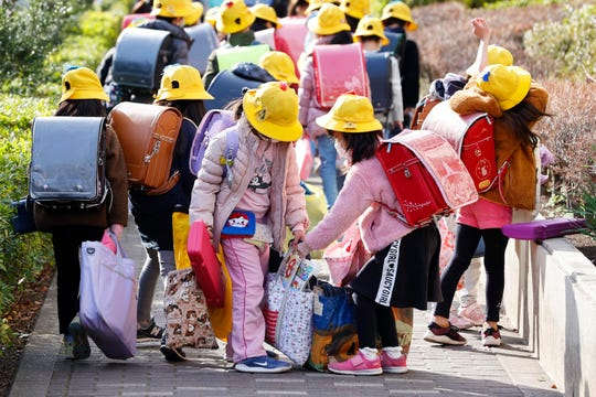 Elementary school students carry their belongings as they make their way home in Tokyo Friday. The expectation that Japan would close all its elementary, secondary and high schools will send nearly 13 million children home.