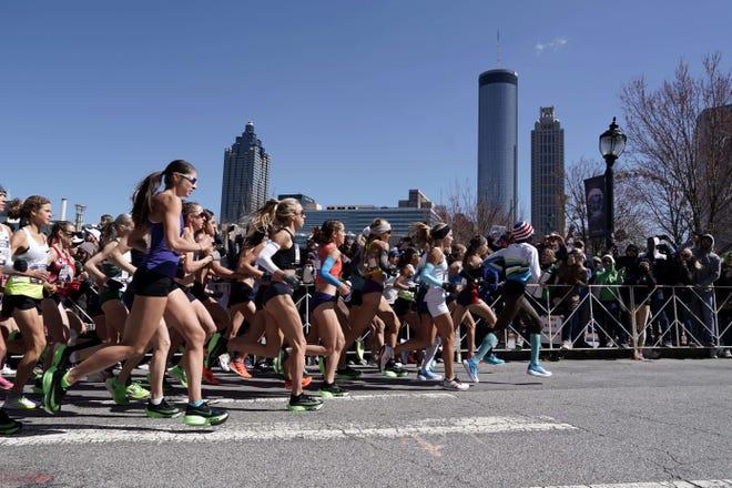 Women's runners run past the downtown skyline during the U.S. Olympic Team Trials marathon Feb. 29, 2020 in Atlanta.