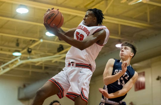 Bosse's Kiyron Powell (52) pulls down a rebound as the Bosse Bulldogs play the Reitz Panthers at Bosse High School Friday evening, Feb. 28, 2020. Bosse won 71-70.
