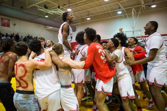The Bosse Bulldogs celebrate their first outright SIAC championship victory since 2006 over the Reitz Panthers at Bosse High School Friday evening, Feb. 28, 2020. Bosse won 71-70.