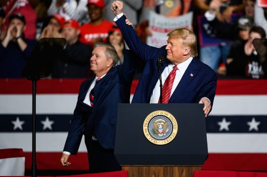 President Donald Trump cheers with Sen. Lindsey Graham during a rally at the North Charleston Coliseum on Feb. 28.