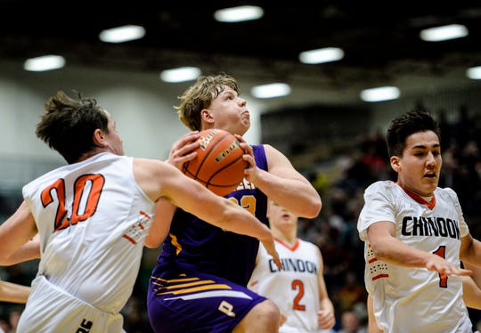 Big Sandy's Kade Strutz goes up for a layup as Chinook's Ethan MacLeod, left, and Ethan Bell defend during the semifinal game Northern C Divisional Basketball Tournament in the Four Seasons Arena, Friday.