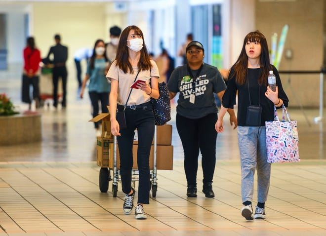 Travelers wear protective face masks within the A.B. Won Pat International Airport in Tamuning on Saturday. Adelup said Sunday that there will be increased medical screenings for South Korean passengers coming into Guam.